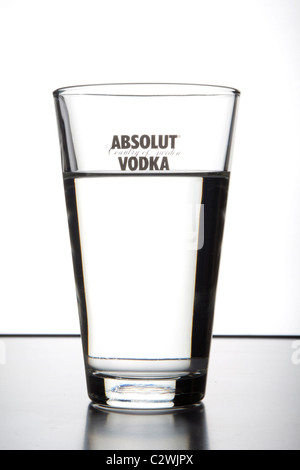Glass with logo of Absolut vodka with liquid in it - Stock Photo