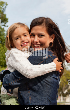Lovely smiling Hispanic mother in jean jacket hugs her happy young daughter who is wearing a white sweater and returns - Stock Photo