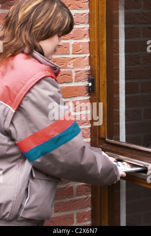 Post delivery service delivering letters at front door - Stock Photo
