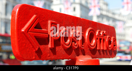 Red Post Office arrowed direction sign on top of post box Regent Street West End London England UK - Stock Photo