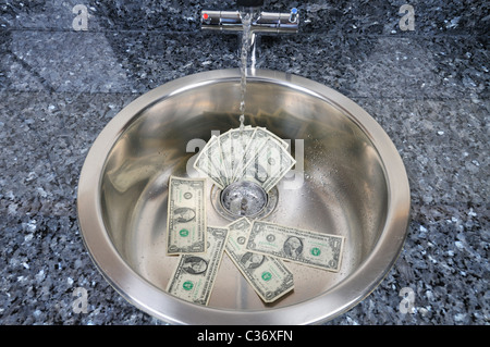 Sink with US dollar bills in drain with water running concept 'money going down the drain' - Stock Photo