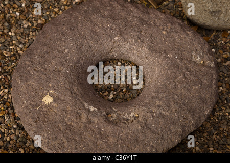 Severely worn Sinagua Indian metate (or mealing stone) at the entrance of Montezuma Castle National Monument, Arizona, - Stock Photo