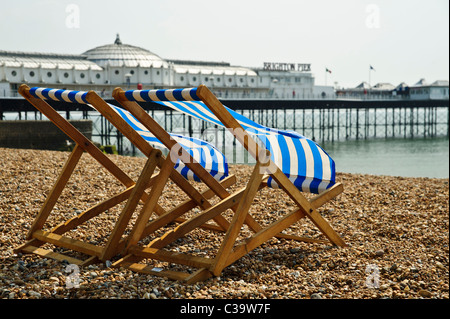BRIGHTON, UK  29/04/2011. Two deckhairs (blue stripe fabric) on Brighton Beach in front of the pier. - Stock Photo