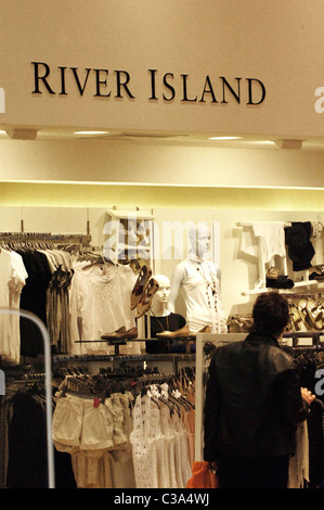 Man browsing inside a River Island store, London, England - Stock Photo