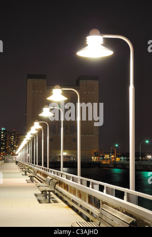 Long pier with lights in the distance. - Stock Photo