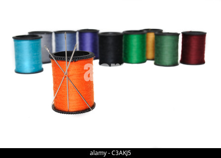Colorful spools of thread with an orange one holding needles in the foreground. - Stock Photo