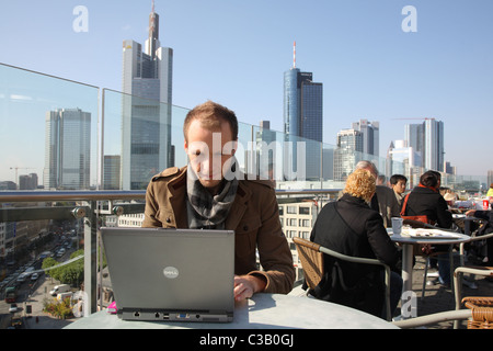 A man with a laptop on a rooftop, Frankfurt am Main, Germany - Stock Photo