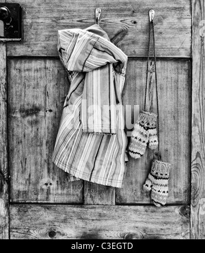 Young Girls striped coat and mittens hanging on a wooden kitchen door. Monochrome - Stock Photo