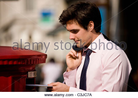 A businessman posting letters in a letterbox - Stock Photo