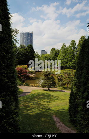 Germany, North Rhine-Westphalia, Bonn, View of Japanese garden with skyscraper in background - Stock Photo