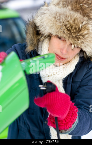 Young woman charging electric car - Stock Photo