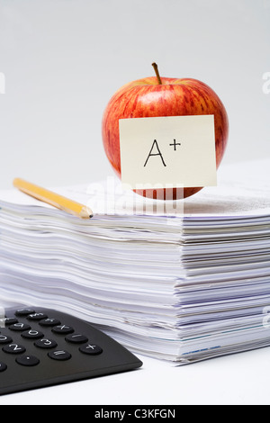 An apple on a stack of paper, close-up. - Stock Photo