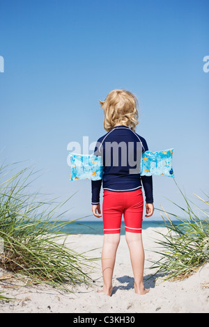 Boy standing on beach with inflatable armband - Stock Photo