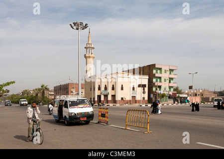 General street scene in Luxor Egypt with local taxi and mine on bike on mobile phone and minaret in background - Stock Photo