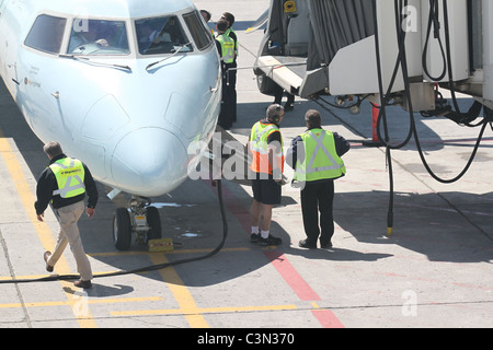 Men working on a plane prepping for departure - Stock Photo