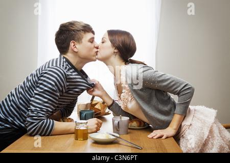 Woman kissing boyfriend over table - Stock Photo