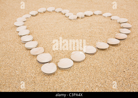 New Zealand,  Clam shells forming heart on sand - Stock Photo