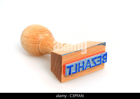 Rubber stamp 'bezahlt' - means paid - in front of a white background - Stock Photo