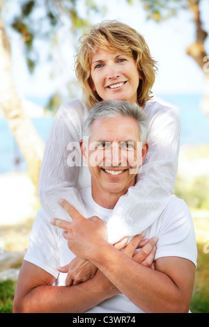 Close-up portrait of a mature couple smiling and embracing. - Stock Photo