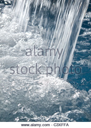 Close up of water splashing into swimming pool - Stock Photo