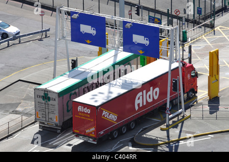 Polish lorry alongside Irish peat hgv both leaving Dover Ferry port passing detector panels - Stock Photo