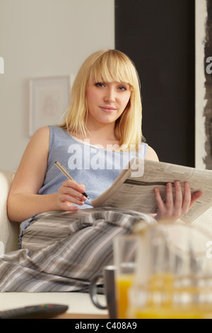 Young woman job-hunting in newspaper - Stock Photo