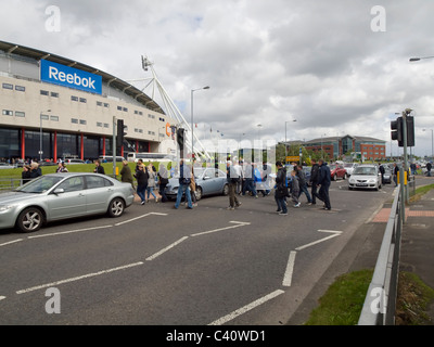 Football fans crossing the road going to the match at the Reebok Stadium, the home ground of Bolton Wanderers football - Stock Photo