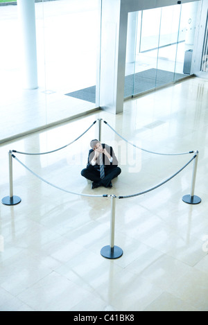 Businessman sitting on floor inside roped off area in lobby - Stock Photo