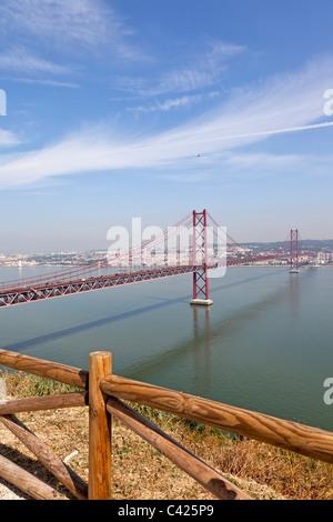 25 de Abril bridge in Lisbon, Portugal. A suspension bridge twin of the Golden Gate bridge and built by the same - Stock Photo
