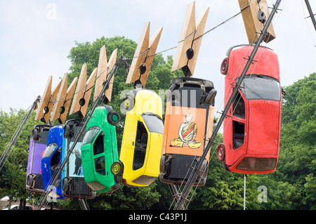 Seven cars hang from giant clothes pegs on a wire in Brighton as part of the annual Art Festival Fringe street theatre. - Stock Photo