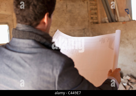 An architect reviewing blueprints at a building site - Stock Photo