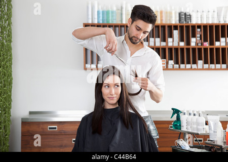 A woman having her hair cut by a male hairdresser - Stock Photo