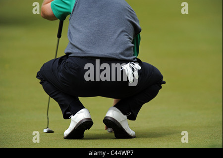 A Golfer lines up a putt on a Green - Stock Photo