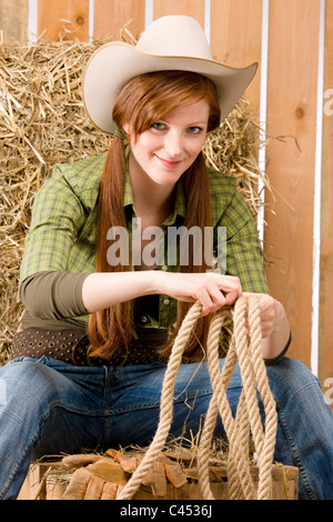Young cowgirl western country style sitting in barn - Stock Photo