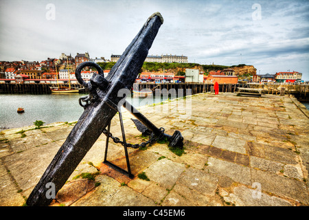 Whitby, Yorkshire, England old anchor on harbour wall looking over the estuary to the town - Stock Photo