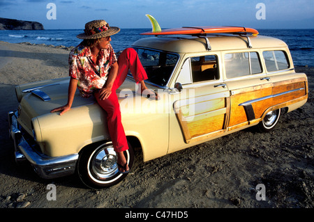 A California surfer relaxes on his classic 1952 Mercury woodie station wagon as the sun sets over the Pacific Ocean - Stock Photo
