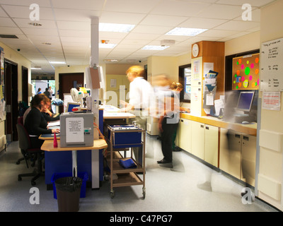 Busy UK NHS Hospital Ward, with doctors and nurses rushing about, blurred, showing movement and action - Stock Photo