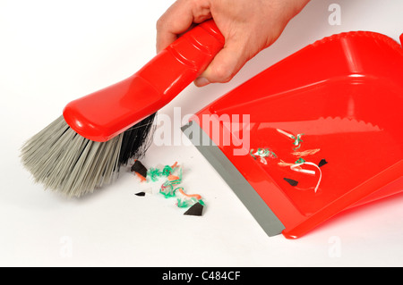 Red brush and dustpan with some garbage on white background - Stock Photo