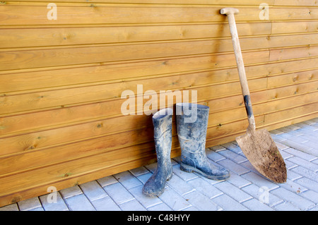 Shovel and gumboots based on a wooden wall - Stock Photo