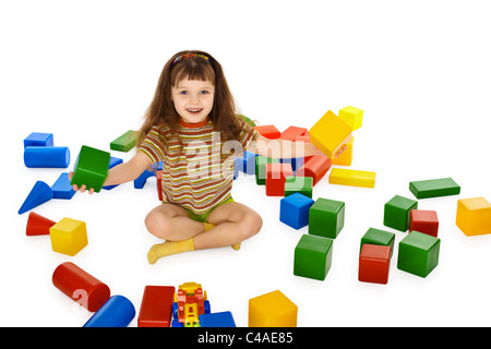 Little girl playing with colored cubes on the floor isolated on white background - Stock Photo