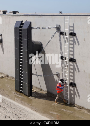 Newly built quay of the deep sea port expansion at Maasvlakte 2 in Rotterdam, the Netherlands, with man climbing - Stock Photo