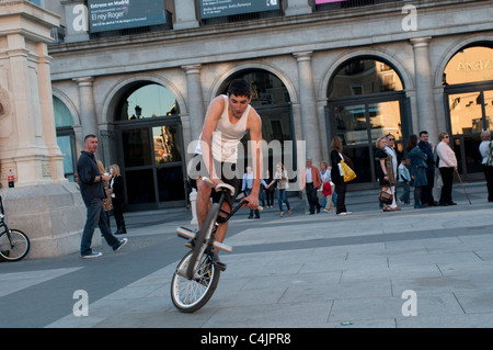 Young man doing acrobatics on his bicycle, Plaza de Isabel II, Madrid, Spain - Stock Photo