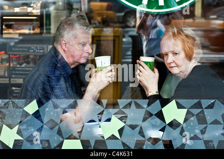 pensive senior couple lost in thought glimpsed through window of Starbucks cafe Manhattan New York City - Stock Photo