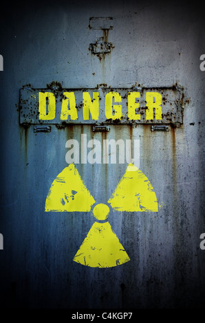 Part of old rusty door with radiation sign and 'danger' word. Radiation contaminated area. - Stock Photo