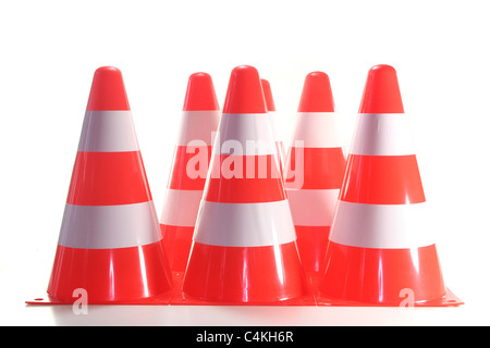 red and white construction pylons before a white background - Stock Photo