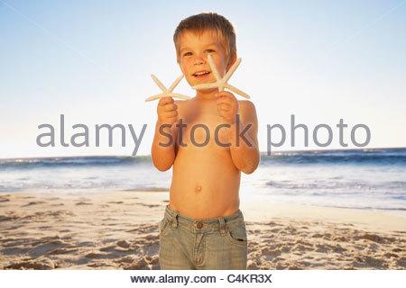 Boy holding starfish on beach - Stock Photo