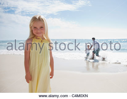 Girl standing on beach with father and brother playing in ocean - Stock Photo