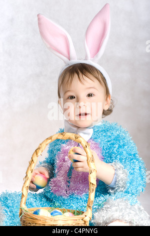 A little boy dressed as bunny and Easter eggs - Stock Photo