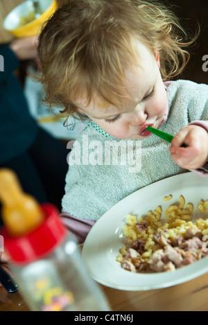 Toddler girl feeding herself - Stock Photo