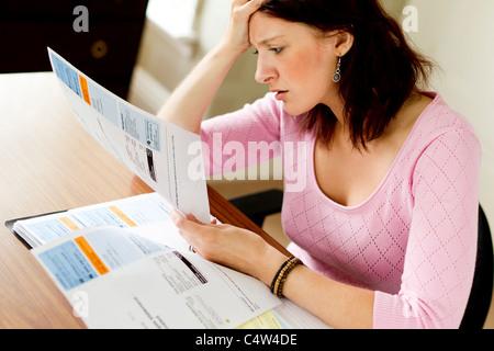 Woman looking at Utility bills - Stock Photo